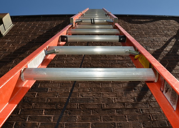 View looking up a ladder placed against a brick wall