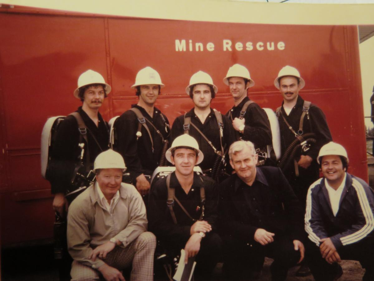 Photo of the Macassa Mine rescue team 1975 Provincial Mine Rescue Competition. Alex Gryska is Number Two man top left corner holding the flame safety lamp. Also Joe MacInnis, kneeling front row, later became the Mine Rescue Officer in Timmins.